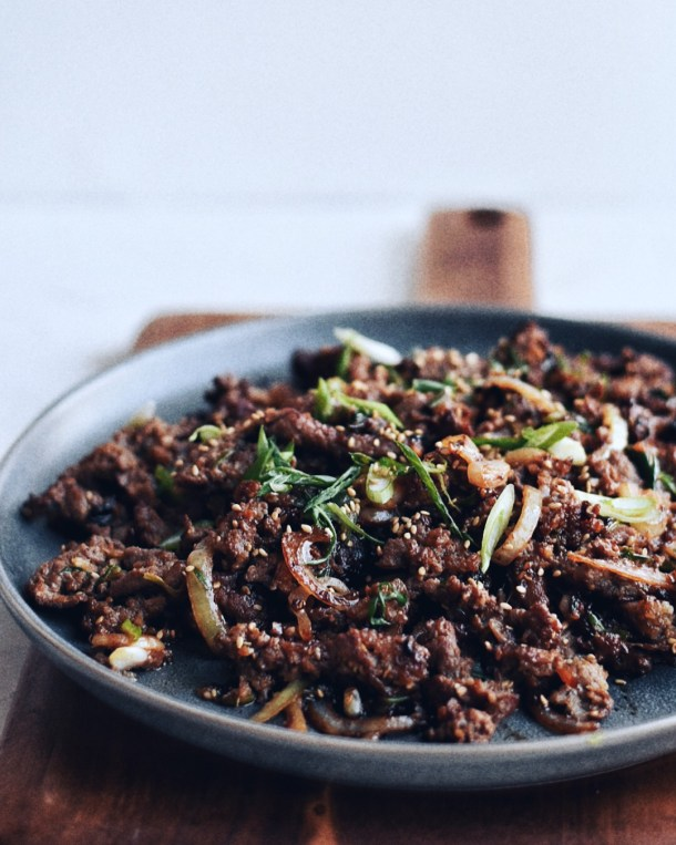 Korean beef bulgogi on a plate with green onions sprinkled on top