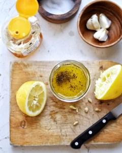 lemon vinaigrette in jam jar on cutting board
