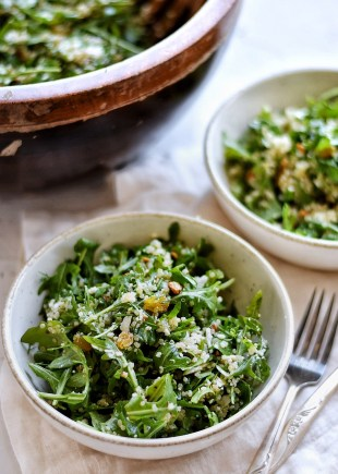 arugula quinoa salad in bowl with fork