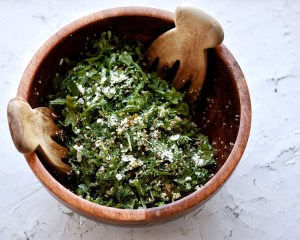 wooden bowl with arugula quinoa salad and serving forks