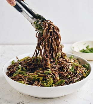 Spicy soba noodles in a bowl with tongs