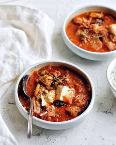 bowl of kimchi stew with a spoon next to another bowl and napkin
