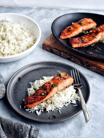 asian glazed salmon and rice on dark plate with fork with rice and salmon in background