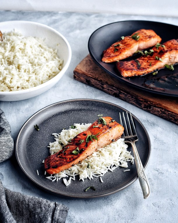salmon and rice on dark plate with fork with rice and salmon in background