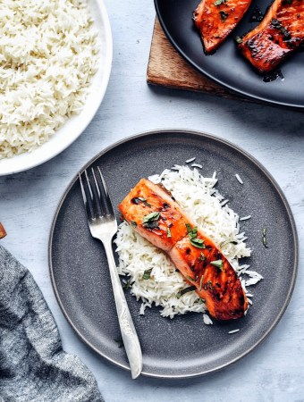 top down shot of plate of asian glazed salmon and rice with fork and rice in corner
