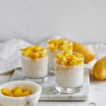 three cups of coconut sago with mango on cutting board with bowl of mangoes in front
