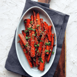 gochujang roasted carrots on oval platter with grey napkin and cutting board