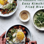 bowl of kimchi fried rice with hands holding it and small bowl of sesame seeds and green onions on the side