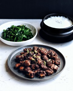 plate of asian pork riblets with pot of rice and plate of green vegetables on the side