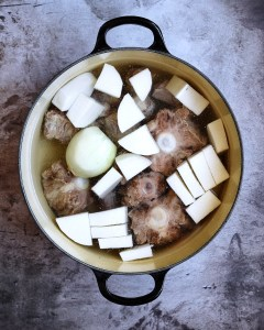 oxtails in pot with onion and daikon, covered with water