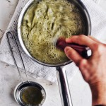 hand whisking green liquid in small saucepan