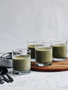 glass cups filled with matcha coconut pudding staggered on tray with spoons in foreground