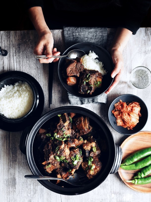 hands holding bowl of Korean braised short ribs and rib at table set for a meal