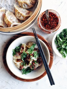 bowl of dumplings covered in chili oil and silantro with more chili oil, cilantro, and dumplings on the side