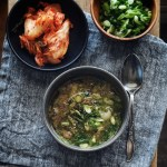 bowl of korean beef bone soup with sides of kimchi and more green onion