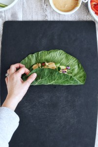 hand wrapping up an Asian Collard Wrap on black cutting board