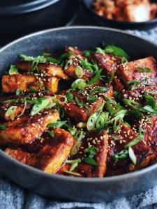 close up of dubu jorim with bowl of kimchi in the corner