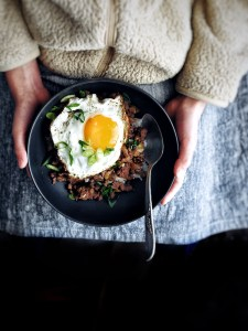 two hands holding a bulgogi bowl with a fried egg on top