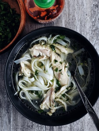 lemongrass chicken soup in black bowl with spoon