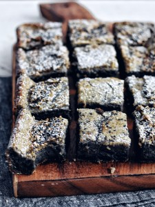 black sesame mochi cake on cutting board with bite taken out of one piece