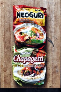 two packages of Korean instant noodles on wood background; Chapagetti and Neoguri