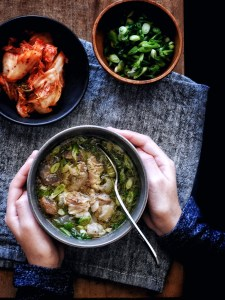 two hands holding a bowl of korean beef bone soup (gomtang)