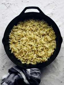 grated potatoes in cast iron skillet