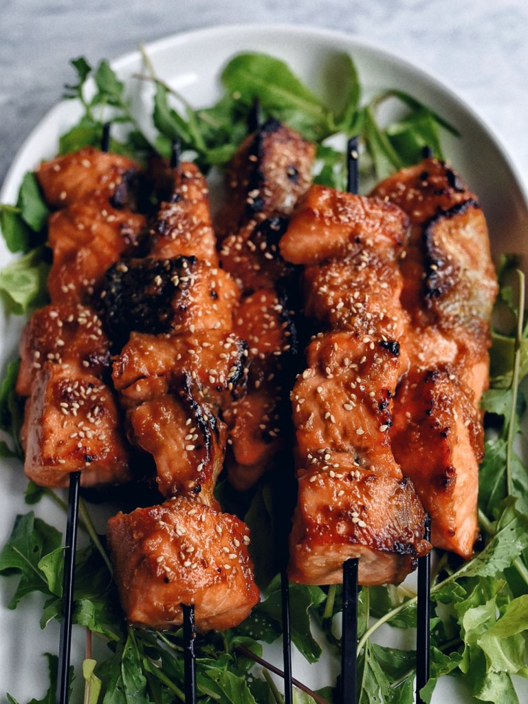 miso salmon skewers on bed of arugula