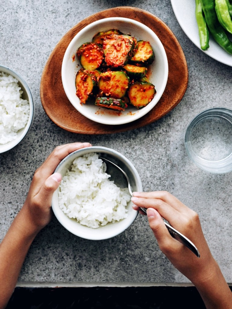 two hands eating bowl of rice with Korean Cucumber Pickle (Oi Muchim) nearby
