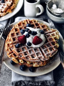 stack of buttermilk waffles with black sesame whip and berries