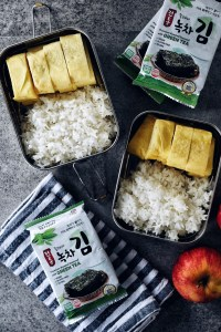 two lunchboxes filled with rice and Korean rolled Omelette
