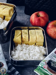 Stainless steel lunch container filled with rice and Gyeran Mari (Korean Omelette)