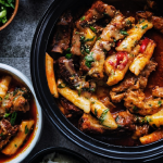 black pot filled with spicy galbi jjim with another bowl on the side