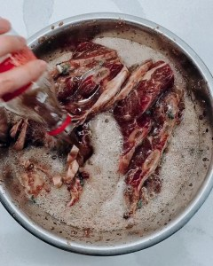 Coca Cola being poured in large bowl of Korean galbi