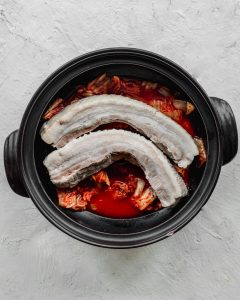parboiled pork belly in pot with kimchi