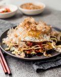 Japanese Okonomiyaki on grey plate with chopsticks