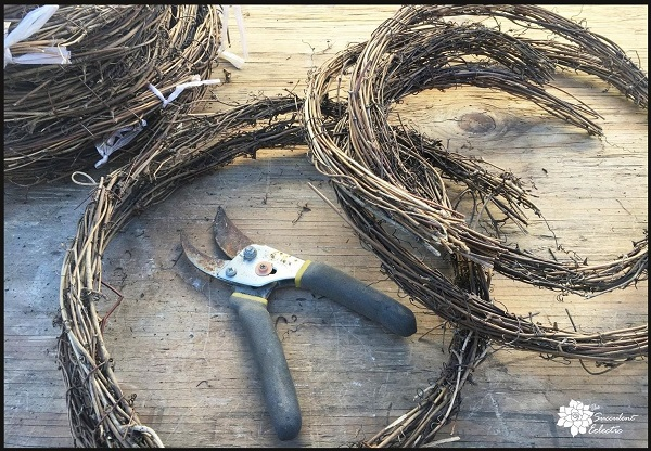 cutting twig garland to make a grapevine heart wreath