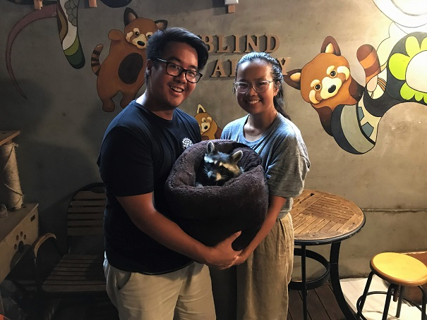 Adi-and-Shelly-holding-a-racoon-at-Blind-Alley