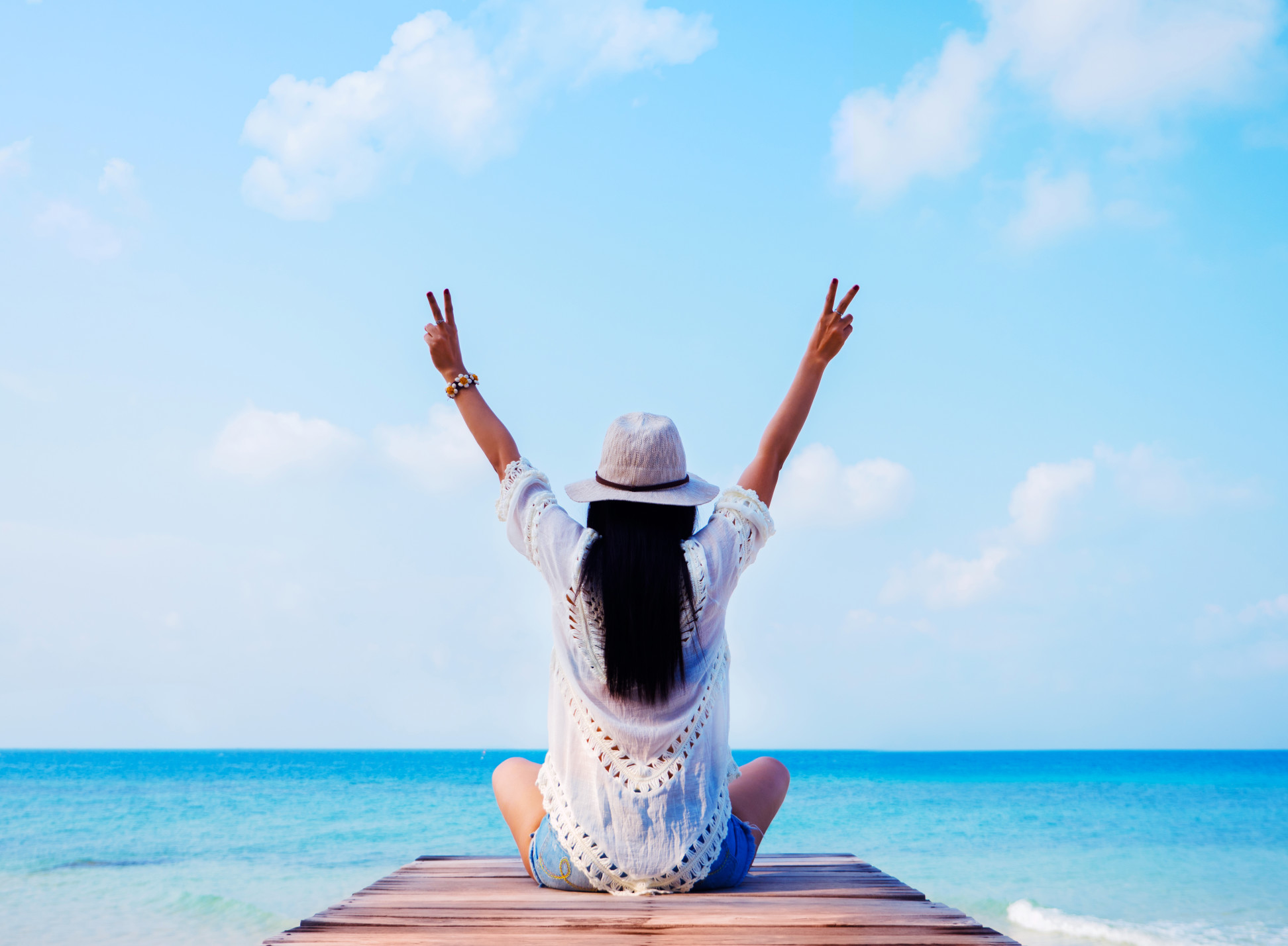 woman-in-sunhat-with-raised-hands-sitting-and-looking-at-sea