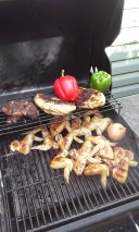 Photo: Split chicken breats, chicken wings, lamb shoulder chops, peppers and onions on the grill.