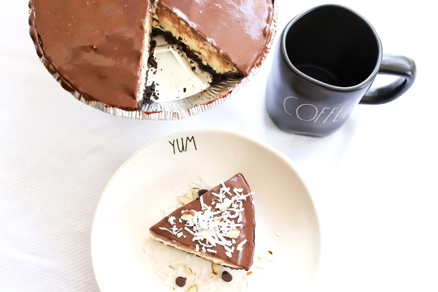 almond joy ice cream pie with one slice on the side, featuring toasted coconut and almond ice cream topped with chocolate ganage