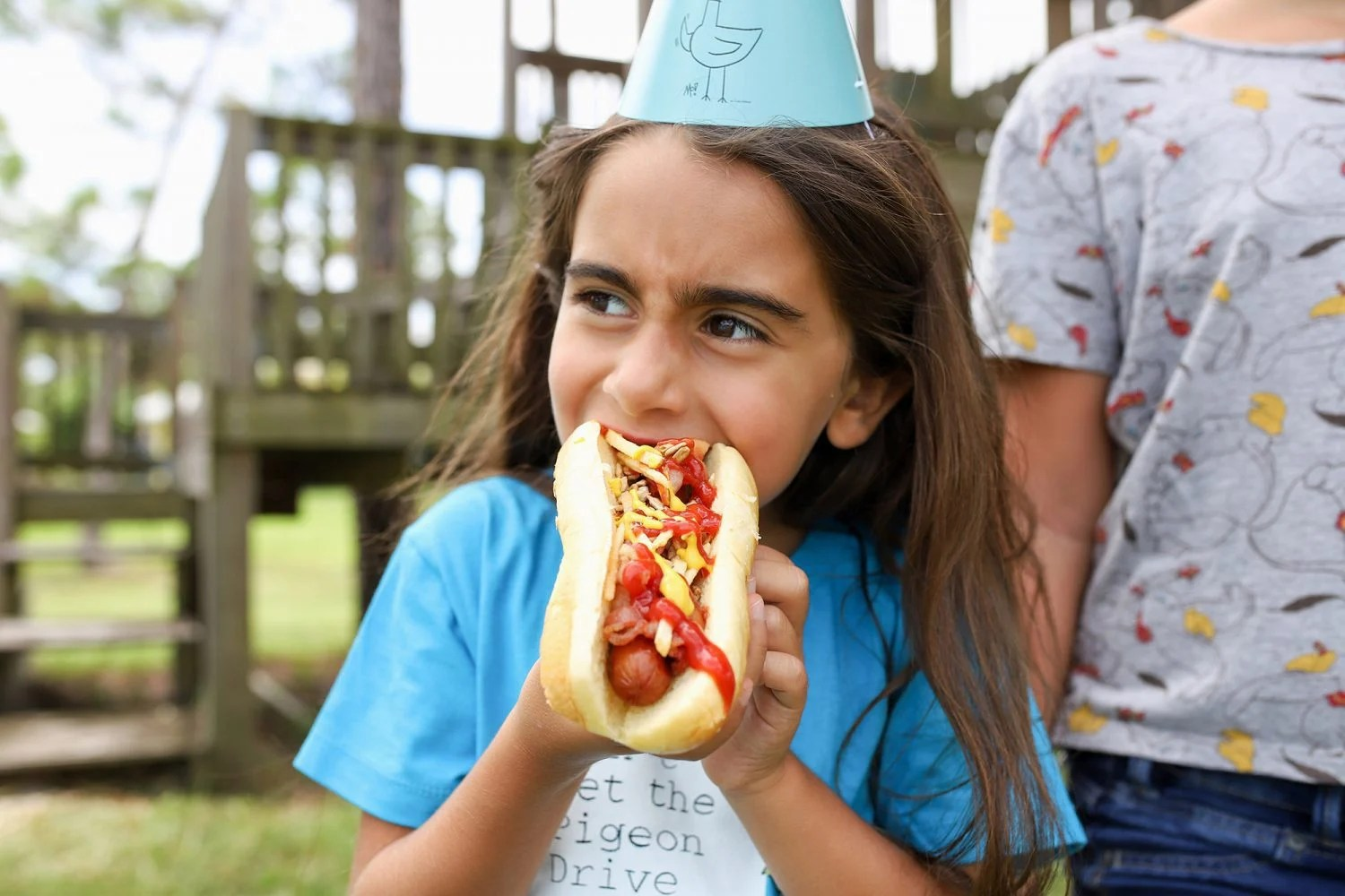girl eating a hot dog with a mo willems pigeon birthday hat on