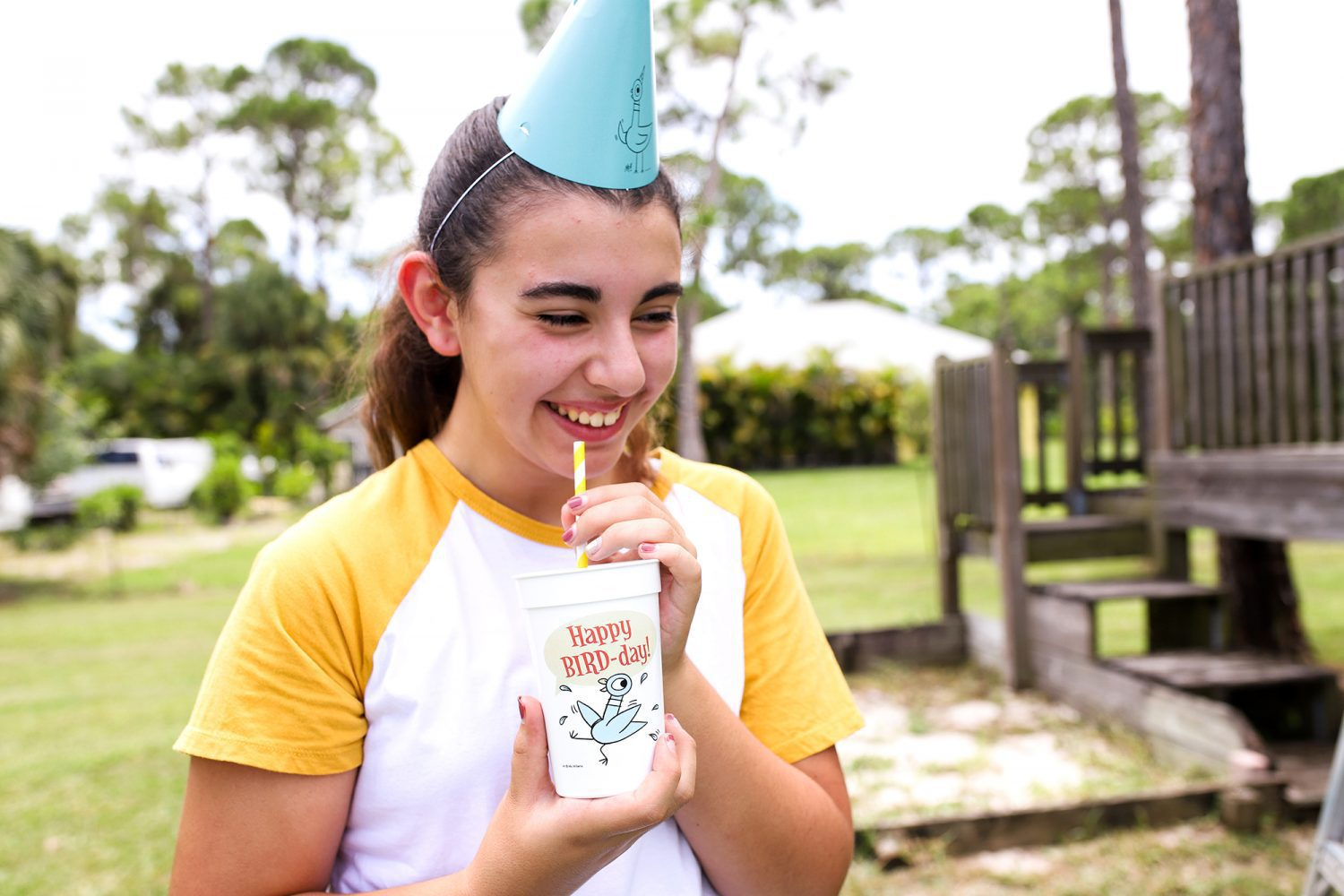 smiling girl holding a mo willems pigeon bird day cup and wearing a pigeon bird-day hat