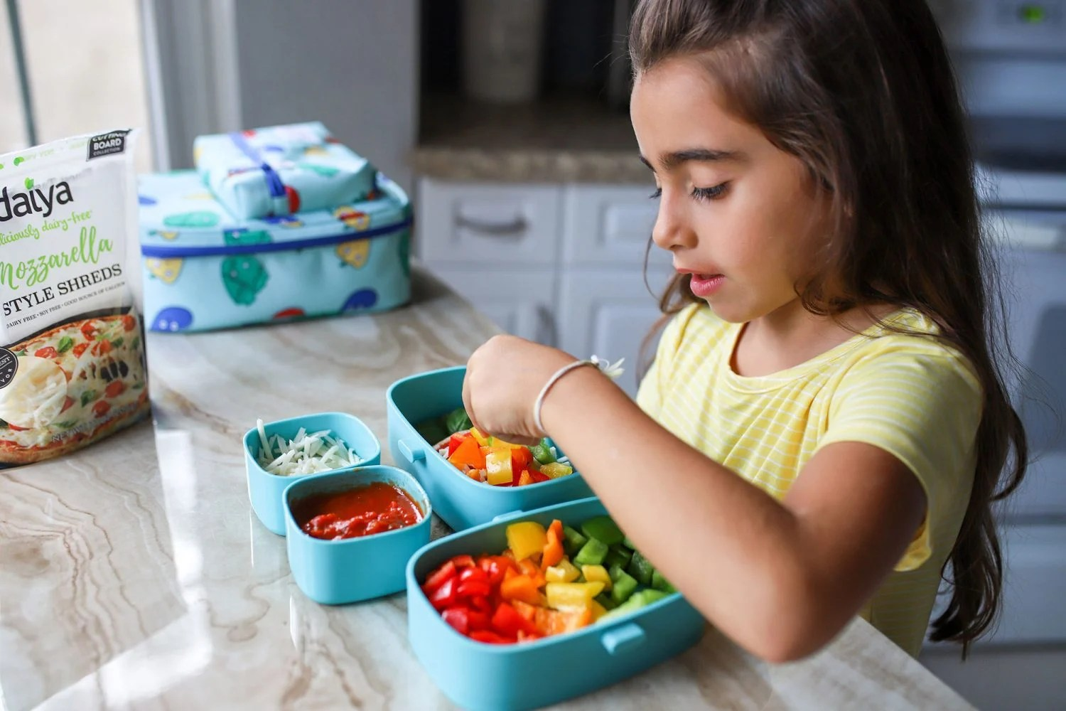 young girl creating a dairy free pizza
