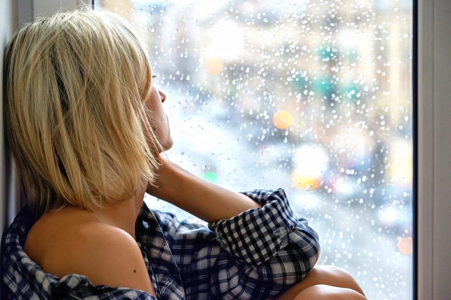 Depressed woman sitting and looking out of a window