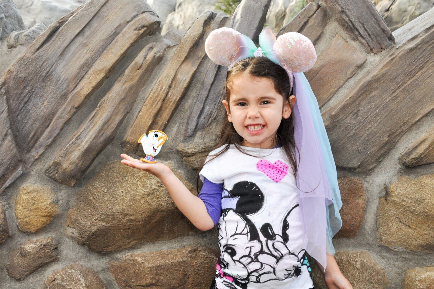 girl at disney world holding chip from beauty and the beast