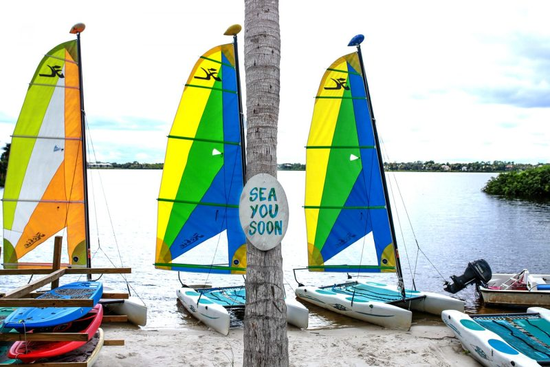 sea you soon sign on the beach with two sailboats