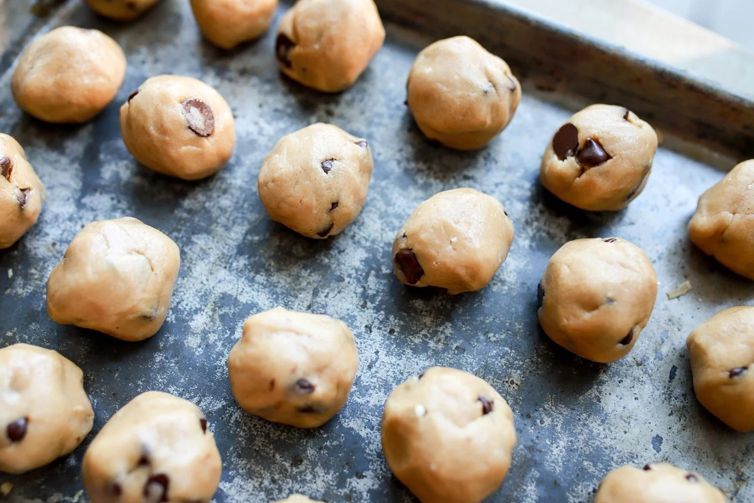 cookie dough balls on a cookie sheet