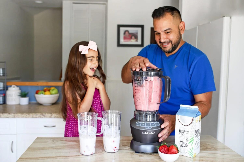girl and her dad blending a drink in a nutribullet