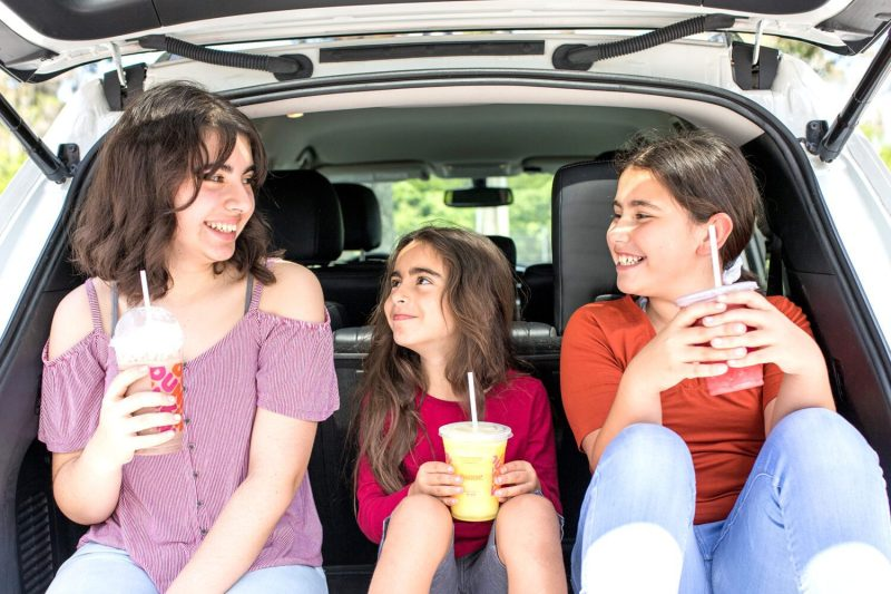 three girls sitting in the back of an SUV enjoying a drink from Dunkin